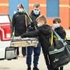 Des enfants et un père déposent du matériel de hockey à l'arrière d'un camion. Ils portent tous un masque.