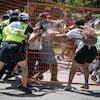 On voit la police repousser des manifestants qui se trouvent derrière une grille.