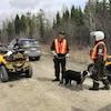 Des policiers sur une route de forêt se tiennent à côté de véhicules quatre roues.
