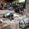 Des manifestants casqués et portant des masques à gaz sont couchés ou assis près d'un chariot contenant des dizaines de cocktails Molotov.