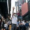 Des hommes et des femmes en tenue de ville sont rassemblés à l'extérieur. Plusieurs lèvent la main droite en l'air.