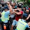 Un policier lève sa matraque pour frapper un homme parmi plusieurs personnes qui sont massées devant lui.