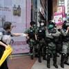 Une femme interpelle des policiers en tenue antiémeute dans une rue de Hong Kong.