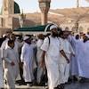 Des hommes vêtus de blanc portent la dépouille de Ben Ali recouverte d'un linceul vert.