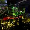 On voit une série de rayons laser rouges, jaunes et verts qui sont reflétés et passent à travers divers instruments.