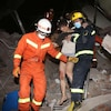 Des sauveteurs aident une femme blessée à sortir des décombres d'un immeuble effondré.