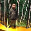 Un enfant est photographié debout, souriant, face à la caméra.
