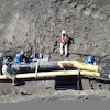 Vue aérienne de travailleurs réparant un pipeline.