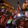 Deux travailleurs d'Hydro-Québec réparent un poteau endommagé par les intempéries, à l'aube.