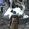 Un personnage dans un jeu vidéo marche sur de la pierre grise et fait face à une sculpture avec un corbeau au loin.