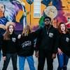 Six jeunes portant des cotons ouatés noirs inscrits douce rebelle, devant une murale.