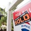 Une maison à l'arrière-plan, une pancarte affichant une maison vendue à l'avant-plan.