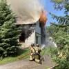 Deux pompiers luttant contre les flammes qui sortent d'une maison.