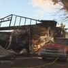 Les ruines d'un garage à la suite d'un incendie. La voiture stationnée contre le bâtiment est aussi endommagée.