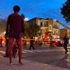 Un homme, de dos, regarde les pompiers à l'oeuvre. Il porte des boxers et se tient nu pied dans la rue.