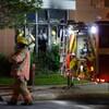 Des pompiers sont à l'oeuvre dans l'établissement; un autre marche tout près.