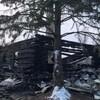 Une maison en rondins des bois ravagée par les flammes.
