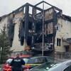 Un policier se tient devant un immeuble partiellement détruit par un incendie