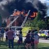 Des personnes dans la rue observe des résidences en feu.