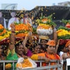 Des femmes portent sur leur tête des vases remplis de fleurs orange, la couleur du BJP.
