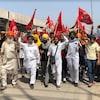 Manifestation d'agriculteurs brandissant des drapeaux et le poing.