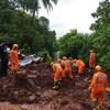 Des hommes en combinaison orange cherchent des corps dans la boue.