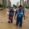 Deux secouristes, l'un tenant une petite fille dans ses bras, marchent vers la caméra dans une rue inondée.