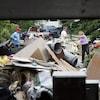 Des personnes amènent des débris à un tas gigantesque de restes de meubles et autres débris.