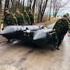 Des militaires transportent un bateau pneumatique.