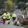 Une équipe d'urgence avance parmi les débris.