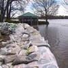 Des digues faites de sacs de sable repoussent l'eau de la rivière des Prairies.
