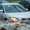 Image d'une voiture prise par les eaux sur une route.