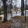 Un résident de North Bay en kayak devant sa maison entourée d'eau.
