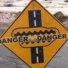 Un panneau de signalisation indique que des inondations peuvent se produire sur la chaussée.