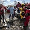 Des secouristes aident une femme à se déplacer sur un pont de bois temporaire.