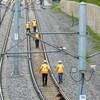 Des hommes marchent le long d'une voie ferrée.