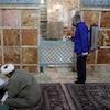 Un employé portant un masque désinfecte un sanctuaire. Deux religieux sont assis par terre et étudient.
