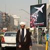 Un religieux marche près d'une affiche montrant des coeurs relâchés par un avion.