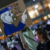Une manifestante tient une pancarte imitant une carte de Monopoly sur laquelle apparaît un dessin d'un policier et la mention, en anglais, « Allez en prison ».