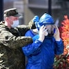Un spécialiste de l'armée russe est aidé pour enlever son équipement de protection.