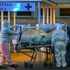 Des travailleurs de la santé en tenue de protection font entrer un patient dans un hôpital.