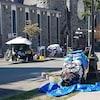 Des tentes sont installées sur le trottoir. Une femme est assise dans l'herbe à côté d'un chariot recouvert de tissus.