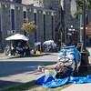 Des tentes sont installées sur le trottoir. Une femme est assise dans l'herbe à côté d'un charion recouvert de tissus.