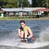 Un jeune homme faisant du ski nautique assis sur un équipement spécialisé.