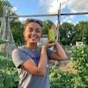 Madison Pierce pose pour la caméra dans un jardin. Elle a un concombre dans les mains qu'elle montre fièrement.