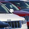 Plusieurs VUS de marque Jeep Grand Cherokee alignés chez un concessionnaire.