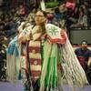 Une jeune femme, debout, dans son costume de danse traditionnel coloré, lors d'une compétition de pow-wow.