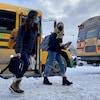Des étudiantes débarquent de l'autobus, masquées, près d'une école de Québec.