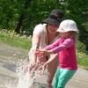 Une mère et sa fille dans un jeu d'eau.