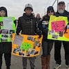 Des personnes rassemblées sur une route et qui tiennent des pancartes.